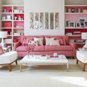 a pink and white mid-century modern living room with built-in shelves with backing and floral artworks