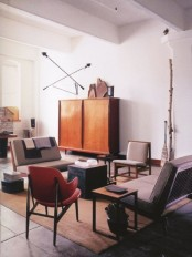 a mid-century modern living room with grey and creamy furniture, a plywood cabinet and some catchy lamps