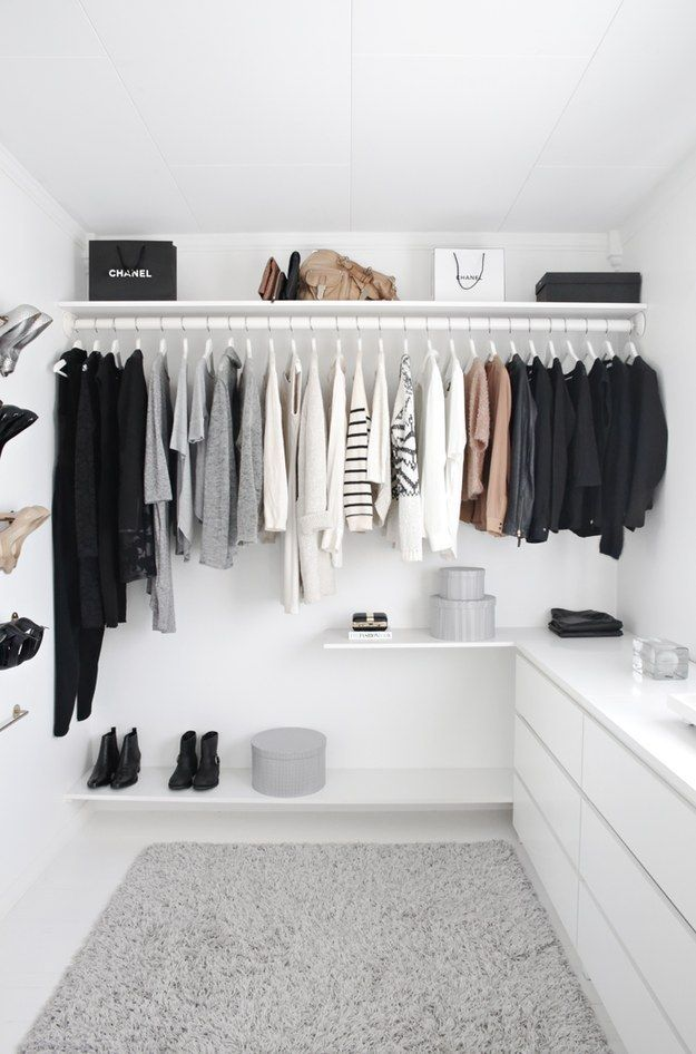 a white minimalist closet with shelves, shoe shelves and some dressers in white to store smaller things and accessories
