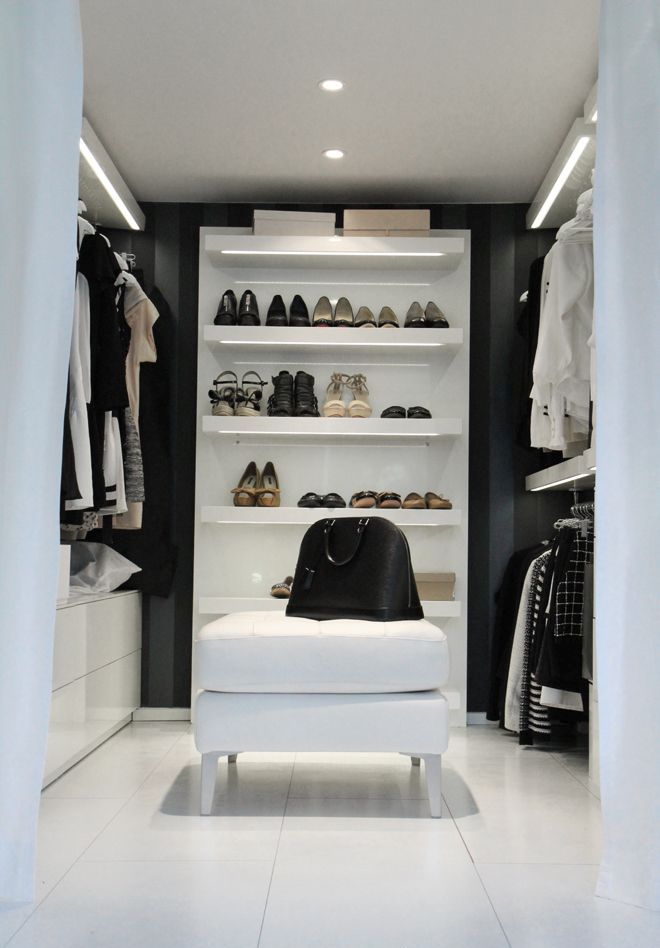 a minimalist black and white closet with hangers, open shelving and some sideboards plus lights