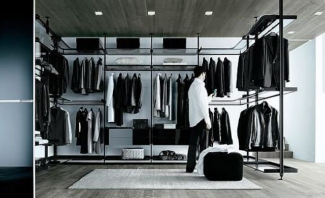 a minimalist masculine closet done with lots of hanger holders and some open shelves plus a couple of baskets