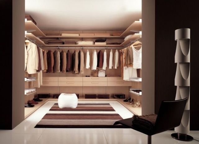 a minimalist closet done of neutral colored plywood, lots of lights and a striped rug for a cozy touch