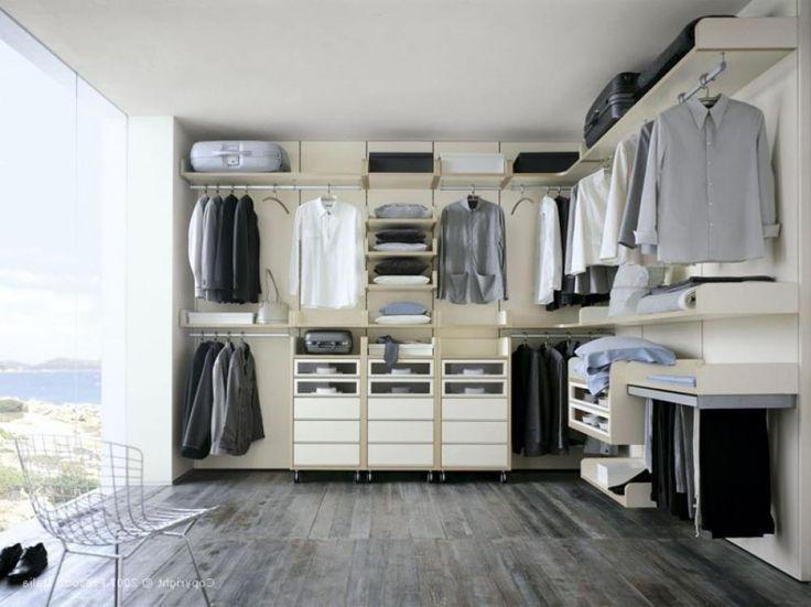 a minimalist closet with a glazed wall, open holders for clothes hangers and some shelves and drawers