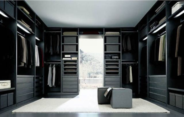 a minimalist closet done in black, with a white rug in the center and lots of drawers and open shelving