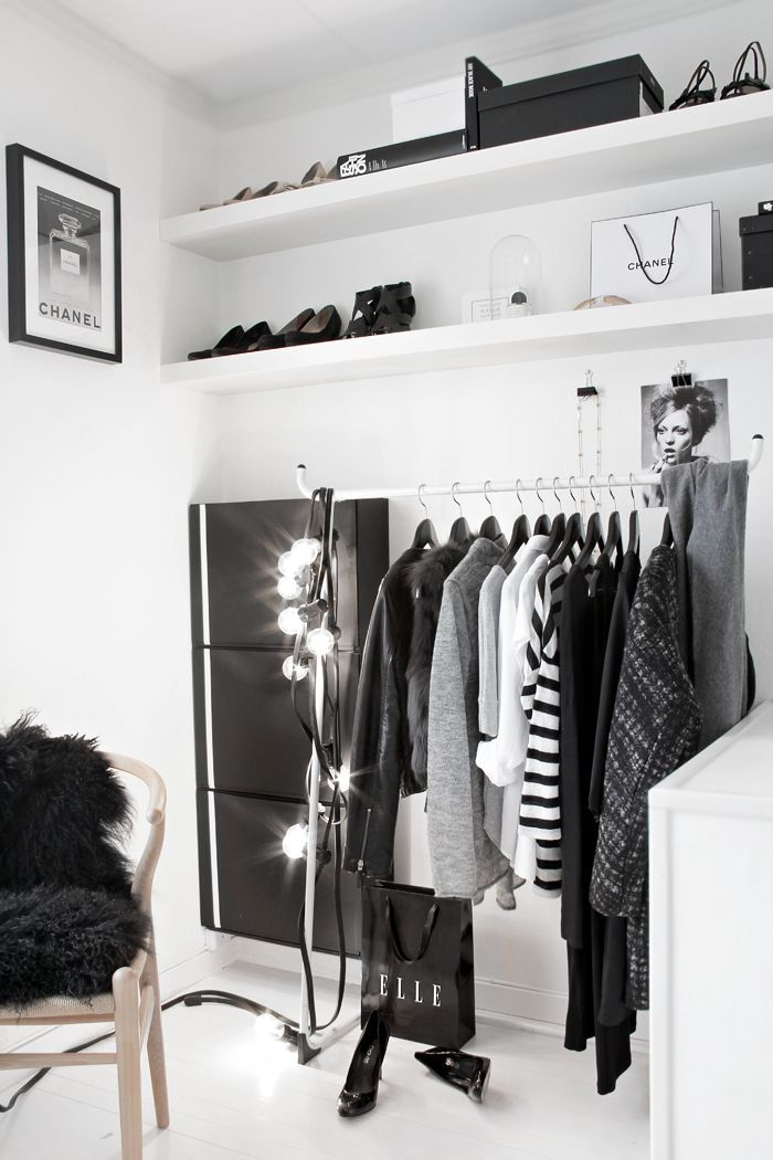 a minimalist white closet with a makeshift closet and open shelves plus lots of lights and a dresser
