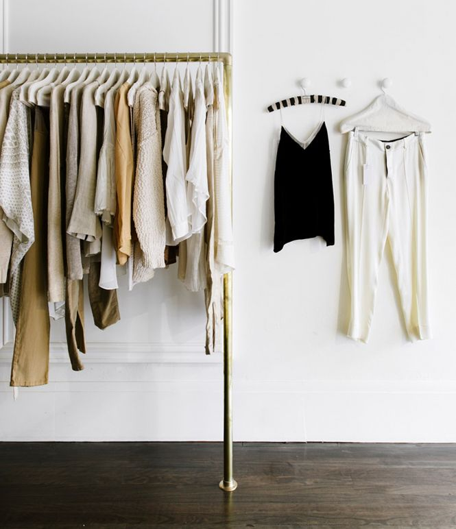 a stylish makeshift closet in gold with some holders for clothes hangers is a simple and modern idea