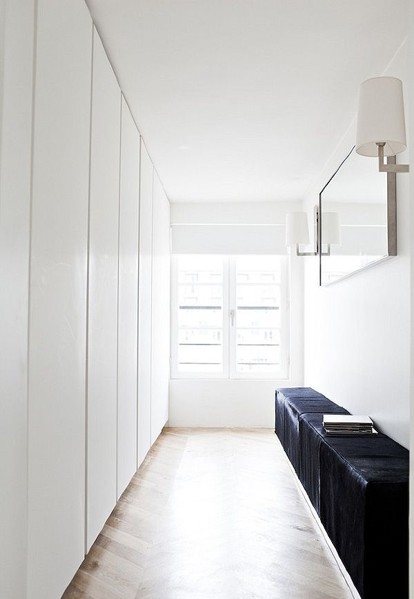 an ultra minimalist closet with lots of wardrobes done in white, with sleek panels and a black leather bench
