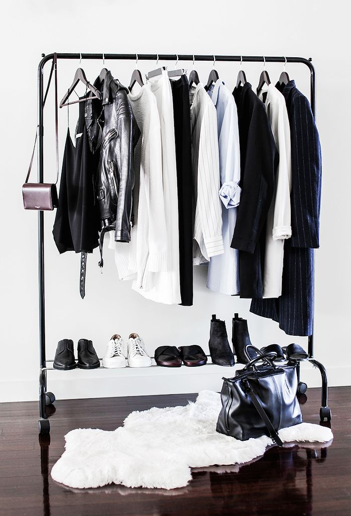 a black makeshift closet with a shoe shelf and a faux fur rug for a Nordic or modern space