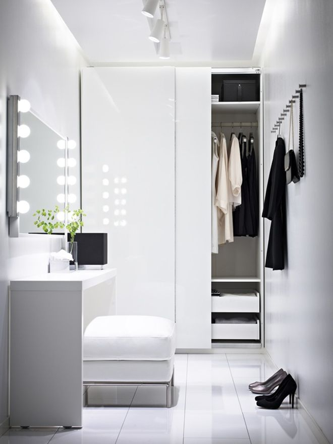 an ultra minimalist closet in white with a storage unit with sliding doors, some drawers, a comfy makeup unit