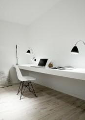 a clean minimalist home office with a floating desk, a white chair and black sconces is a stylish space for comfortable working