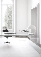 a minimalist home office with a sleek glass corner desk, a stylish chair and a quirky table lamp are all you need to work and enjoy working