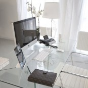 a sophisticated minimalist home office with a clear glass desk, a white chair, a floor lamp and some gadgets is an ultimate workspace