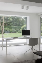 a gorgeous minimalist home office with a floor to ceiling window and a view, a sleek desk and a white chair plus a black bench is a chic space to be