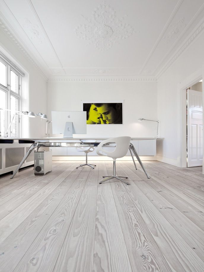 a neutral minimalist home office with a floating storage unit with built in lights, a long desk, white chairs and white gadgets plus table lamps here and there