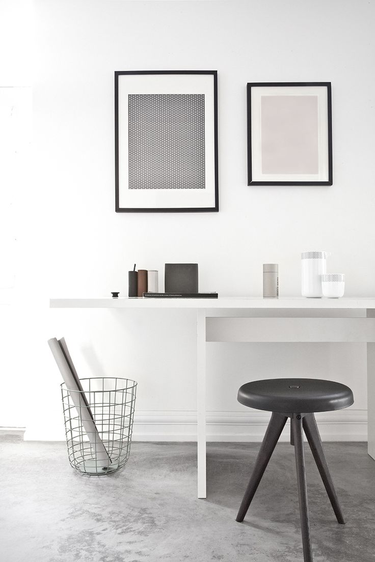 a black and white minimalist home office with a sleek white desk, a black stool, a small gallery wall and a bit of decor
