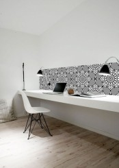 a stylish minimalist home office with a long floating desk, black sconces and a mosaic tile backsplash plus a white chair