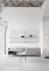 a pure minimalist home office with open shelves, a sleek storage unit, a glass desk and a white chair, some candles and chic decor around