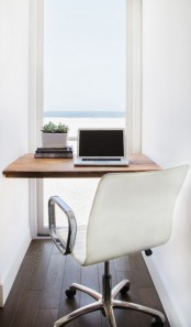 a minimalist home office with a sea view, a built-in desk, a white chair, a stack of books and a potted plant is very sleek and cool