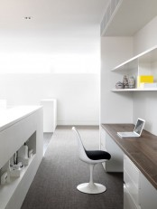 a minimalist home office with a built-in storage unit and a desk in it, a comfy white chair and a large storage unit with a niche