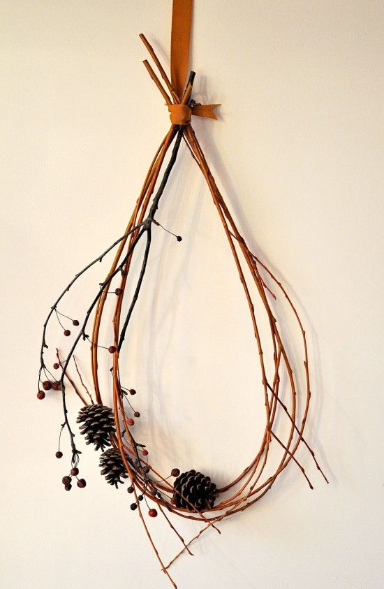a modern and simple Thanksgiving decoration of twigs and pinecones can be hung on the wall or front door