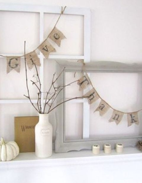 burlap buntings, a vase with a branch arrangement, white pumpkins and candleholders