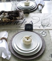 a neutral Thanksgiving tablescape with a neutral table runner, placemats, a basket with pinecones and berries, chalkboard tags