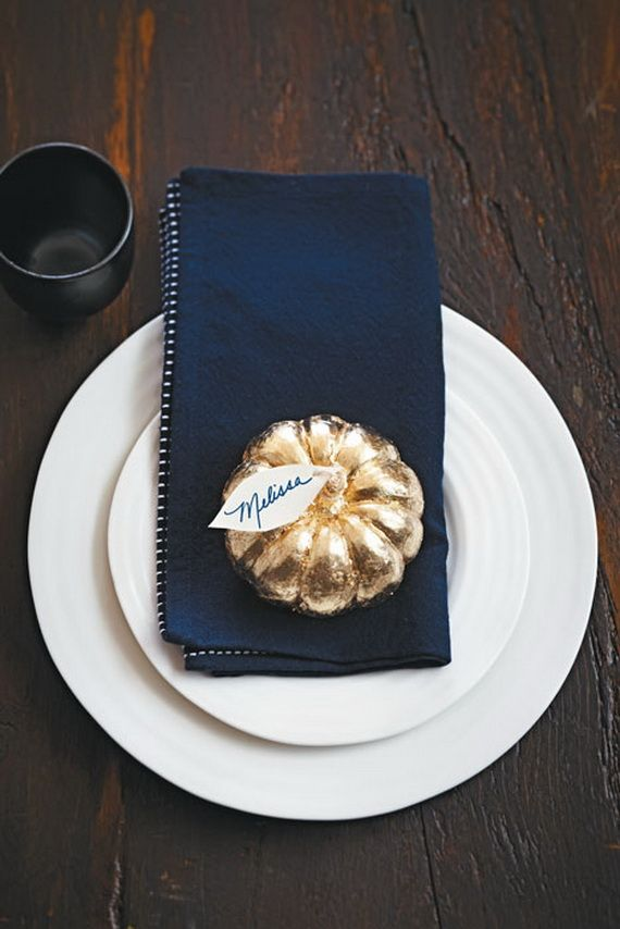 a modern place setting with white plates, a navy napkin, a gilded pumpkin with a tag
