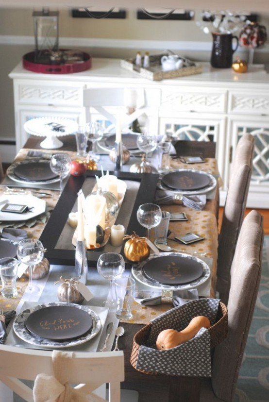 a modern Thanksgiving table setting done in greys, metallic and black, pillar candles and gourds in a basket