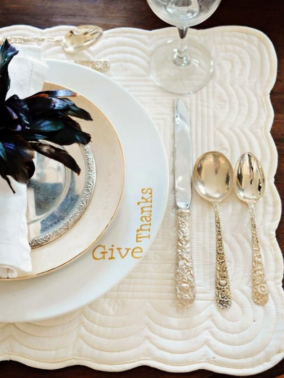 a modern refined place setting with an embroidered placemat, elegant plates and gold cutlery and a black feather arrangement