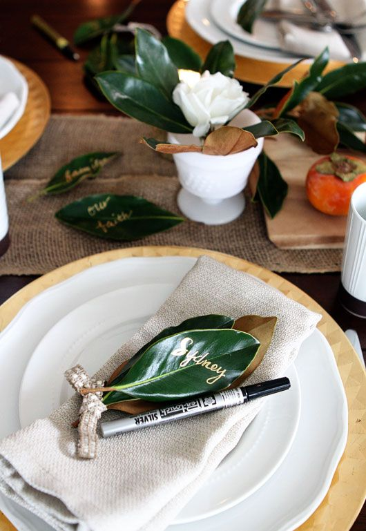 a modern rustic table setting with a burlap runner, foliage, simple plates and chargers