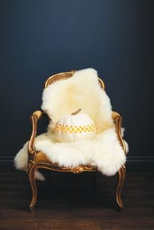 a refined chair with white fur and a large white carved pumpkin is a simple and stylish Thanksgiving decoration