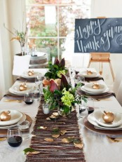 a modern fall or Thanksgiving tablescape with a stick and foliage table runner, brown chargers, gilded apples and dark floral centerpieces