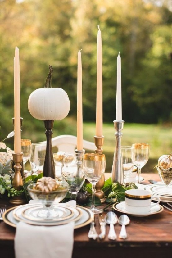 a modern refined Thanksgiving tablescape with thin and tall candles, a greeneyr runner and fresh pumpkins