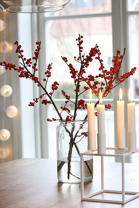 a red berry arrangement in a clear vase and some candles in a modern white candleholder for simple modern decor