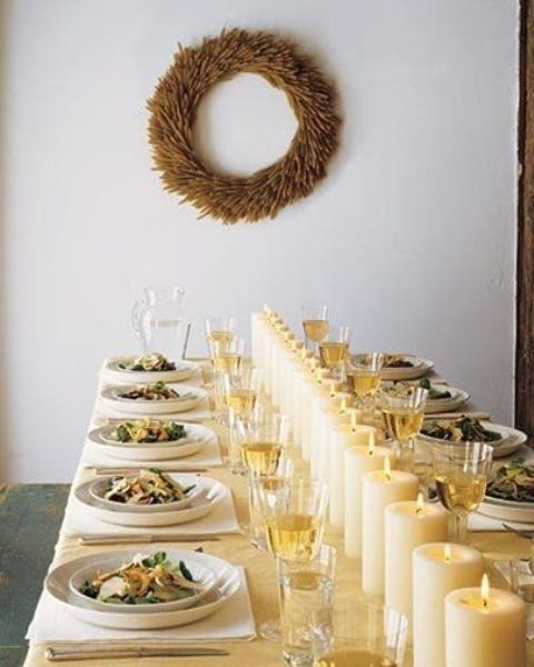 a modern table setting with a row of pillar candles instead of a table runner or centerpiece and a wreath on the wall