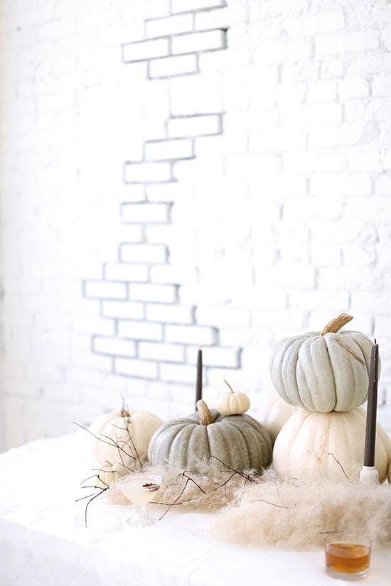 a modern tablescape with heirloom pumpkins, black candles, fur and twigs looks simple, chic and very modern