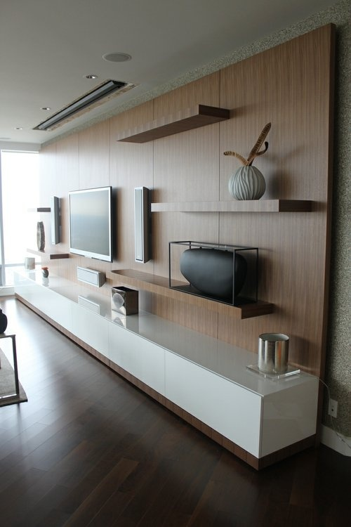 a modern and sleek white TV unit, some floating shelves all attached to a single piece that takes a whole wall