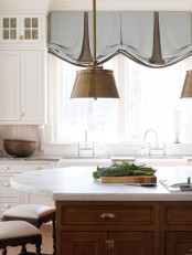 blue and brown Roman shades accent the rustic kitchen and add color to the space matching the brass lamps that wow the kitchen