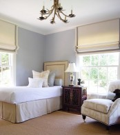 neutral and grey Roman shades highlight the elegance of the bedroom and block out the sun when needed