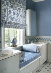 a blue and white print Roman shade is a perfect fit for this coastal bathroom and it keeps it very private and cozy