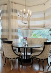striped Roman shades and matching curtains are great to make the dining space welcoming, cozy and private when needed