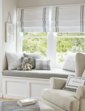 a stylish window nook protected with roman shades