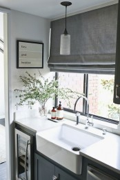 a graphite grey Roman shade is a perfect idea for a Scandinavian kitchen and it makes the space more welcoming and private
