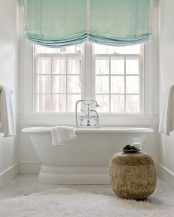 green Roman shades make the bathroom more welcoming and cozy, and adds a delicate touch of color to the space
