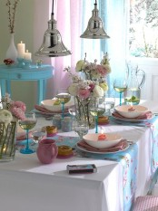 a bright pink and blue spring tablescape with blooms, candles and colorful porcelain