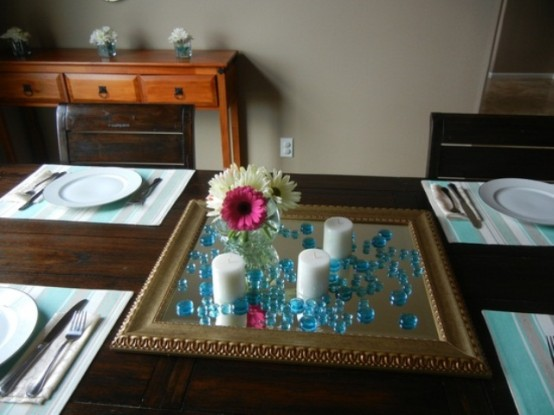 a simple centerpiece of a mirror, blue beads, candles and a colorful bloom centerpiece