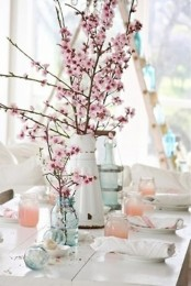 a neutral spring tablescape with ombre peachy pink jars, blue vases and blooming cherry branches
