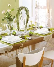 a green and white sprign table setting with green placemats, greenery and bloom centerpieces and little terrariums