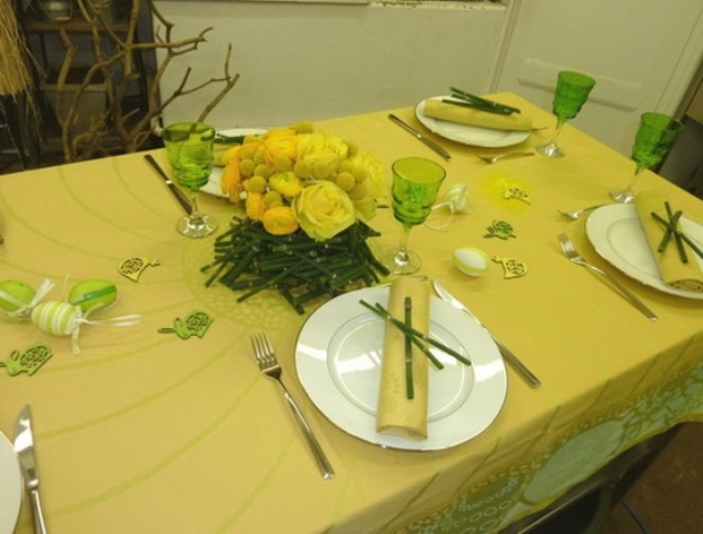 a hot yellow spring tablescape with a bright tablecloth, yellow roses and napkins