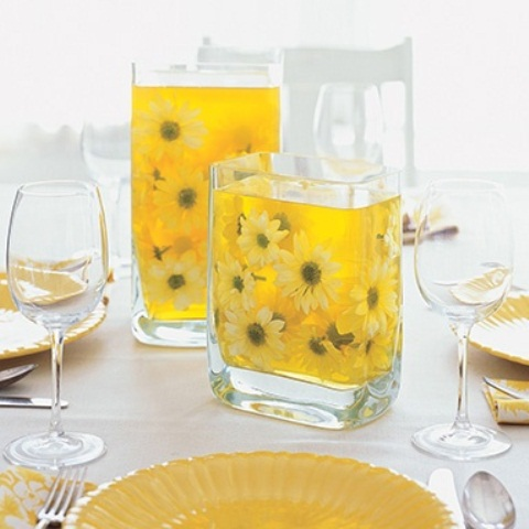 a cheery sprign centerpiece with glasses filled with yellow water and blooms to add color
